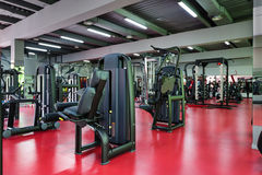 Modern gym interior with equipment. Modern gym interior with machine equipment, red floor and green reflexes from the right, copyspace Stock Photography