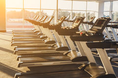 Modern gym interior with equipment, treadmills for fitness cardio training. Modern gym interior with equipment. Fitness club with row of treadmills for fitness Royalty Free Stock Images