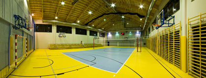 Modern gym interior. Interior of a new modern gym at night. Yellow and blue design elements. Spacious interior wide angle view Stock Photos