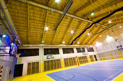 Modern gym interior. Interior of a new modern gym at night. Yellow and blue design elements. Spacious interior wide angle view. Ceiling heater and lights design Royalty Free Stock Images