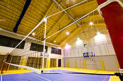 Modern gym interior. Interior of a new modern gym at night. Yellow and blue design elements. Spacious interior wide angle view. Volleyball net detail royalty free stock images