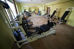 Modern gym interior with various equipment. Empty gym and workout equipment for legs, hands etc Royalty Free Stock Images