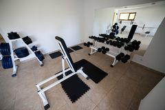 Modern gym interior with various equipment. Empty gym and workout equipment for legs, hands etc Stock Photos