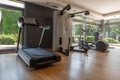 Modern gym with panoramic windows. Sports equipment in the sports room. Different simulators and treadmills indoors. Healthy lifestyle stock image