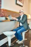 Modern hög affärsman Using Laptop i stång arkivfoto