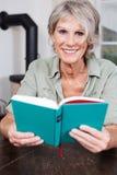 Modern hög dam som läser en bok royaltyfria bilder