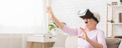 Modern hög kvinna som använder VR-exponeringsglas hemma arkivbild