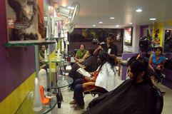 Modern hair dressing saloon. A group of young ladies sets her hair style at an internationally branded beauty parlor in central Kolkata Royalty Free Stock Image