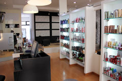 Modern hair salon. Reception, Waiting area, Shelves are stocked with brands and logos showing Royalty Free Stock Photos
