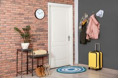 Modern hallway interior with stylish furniture, suitcase and clothes stock image