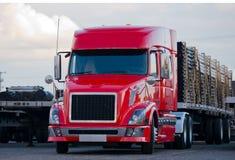 Modern halv släp för plan säng för lastbil med last på parkeringsplats Arkivbilder