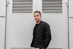Modern handsome nice young man in fashionable black clothes is standing near metal gray doors to enter a modern building. European guy on walking around the royalty free stock image