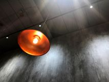 Modern hanging lamp and light bulb. Against cement wall Royalty Free Stock Photo