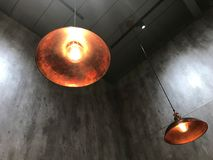 Modern hanging lamp and light bulb. Against cement wall Royalty Free Stock Images