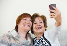 Modern happy mature women using mobile phone Stock Image