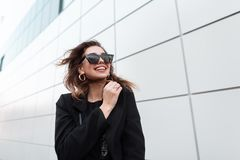 Modern happy young hipster woman in a black stylish coat in dark trendy sunglasses goes and smiles around the city. Near a gray tall building on a spring windy royalty free stock photos