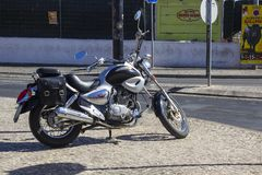 A modern Harley Davidson motor bike with highly polished chrome parts parked on a cobbled street in Albuderia in Portugal Royalty Free Stock Images