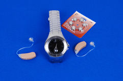 Modern hearing aid. A modern hearing aid and the watch to control the volume of the aid with replaisment batteries on royal blue fabric royalty free stock photos