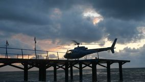 Modern helicopter standing on a wodden pier in the Black Sea shore in slo-mo stock footage