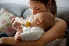 Modern hennes matning behandla som ett barn pojken från flaskan som sitter på soffan a Arkivbild