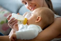 Modern hennes matning behandla som ett barn pojken från flaskan som sitter på soffan a Arkivfoto
