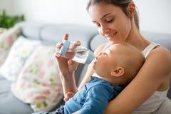 Modern hennes matning behandla som ett barn pojken från flaskan som sitter på soffan a Royaltyfri Fotografi
