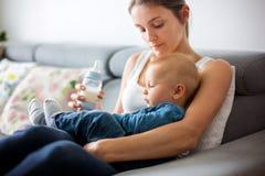 Modern hennes matning behandla som ett barn pojken från flaskan som sitter på soffan a Arkivfoton