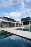Modern herrgård framme av simbassängen med blå himmel arkivbilder