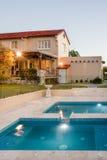 Modern herrgård med blinkande ljus runt om simbassängen royaltyfri bild