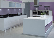 Modern high end luxury kitchen. With white wood doors and black marble work tops Stock Photo
