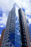 Modern high rise apartment block with clouds reflecting. Modern high rise apartment block rises into the sky, reflecting the clouds on its pristine glass panels Royalty Free Stock Photography