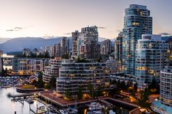 Modern High-rise Apartment Blocks at Twilight. Modern Tall Apartment Buildings in Downtown Vancouver a Twilight.  Some Mountains are Visible in Background Royalty Free Stock Photos