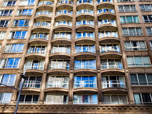 Modern High Rise Apartment Building. Reflections in the complex glazed facade of a modern high rise apartment, or condominium, building, making a semi abstract stock image