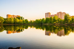 Modern high-rise apartment buildings by the lake at sunset. Summer Royalty Free Stock Photography