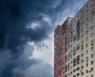 Modern High-Rise Apartment and Cloudy Dark Sky. Single High-rise apartment block facing a dark grey storm cloud Stock Photo