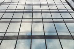 Modern high rise building glass wall with blue sky reflection Stock Photography