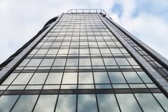 Modern high rise building glass wall with blue sky reflection Royalty Free Stock Photography