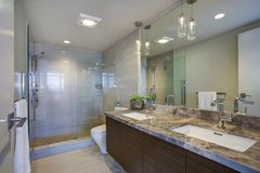 Modern high-rise master bathroom with dual vanity cabinet. Modern high-rise master bathroom features dual vanity cabinet with undermount sinks, grey marble stock photos