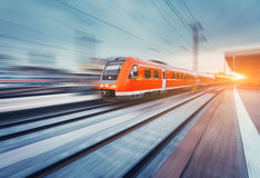 Modern high speed red passenger commuter train. Railway station. Modern high speed red passenger commuter train in motion at the railway platform at sunset Stock Photo