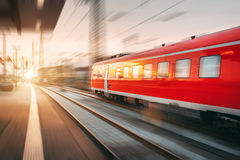 Modern high speed red passenger train moving through railway sta. Tion in the evening. Railway station at sunset in Nuremberg, Germany. Railroad with motion blur stock photos