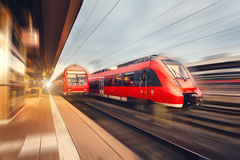 Modern high speed red passenger trains at sunset. Railway statio Stock Photography