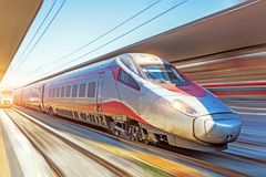 Modern high speed train on a clear day with motion blur at the city station stock images