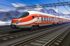 Modern high speed train with motion blur. Red modern high speed train passing snowy mountain railroad station with motion blur effect Stock Photography