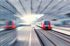 Modern high-speed train. Modern high-speed train moves fast along the platform Stock Photo
