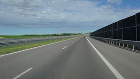 A modern highway with a new marking is shot from a moving car. A fine-looking modern highway with a new marking is shot from a moving car. The road is protected stock footage