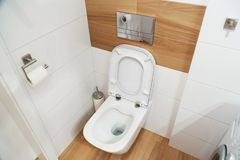 Modern hinged toilet bowl with a tank built into the wall. Opened lid Stock Image