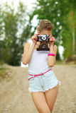 Modern hipster girl photographed using vintage camera. Stock Image