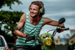 Modern hipster on motobike. Modern hipster man with military headphones on motobike Royalty Free Stock Photography