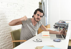 Modern hipster style student or businessman working in stress with laptop at home office angry upset Stock Photo