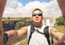 Modern hipster young man taking a selfie at Victoria Waterfalls. During an adventure travel - Trip excursion in Africa Zimbabwe seven nature wonder destination royalty free stock image